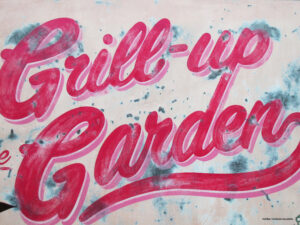 Hand painted Pink and Blue in script that says: Grill- Up Garden