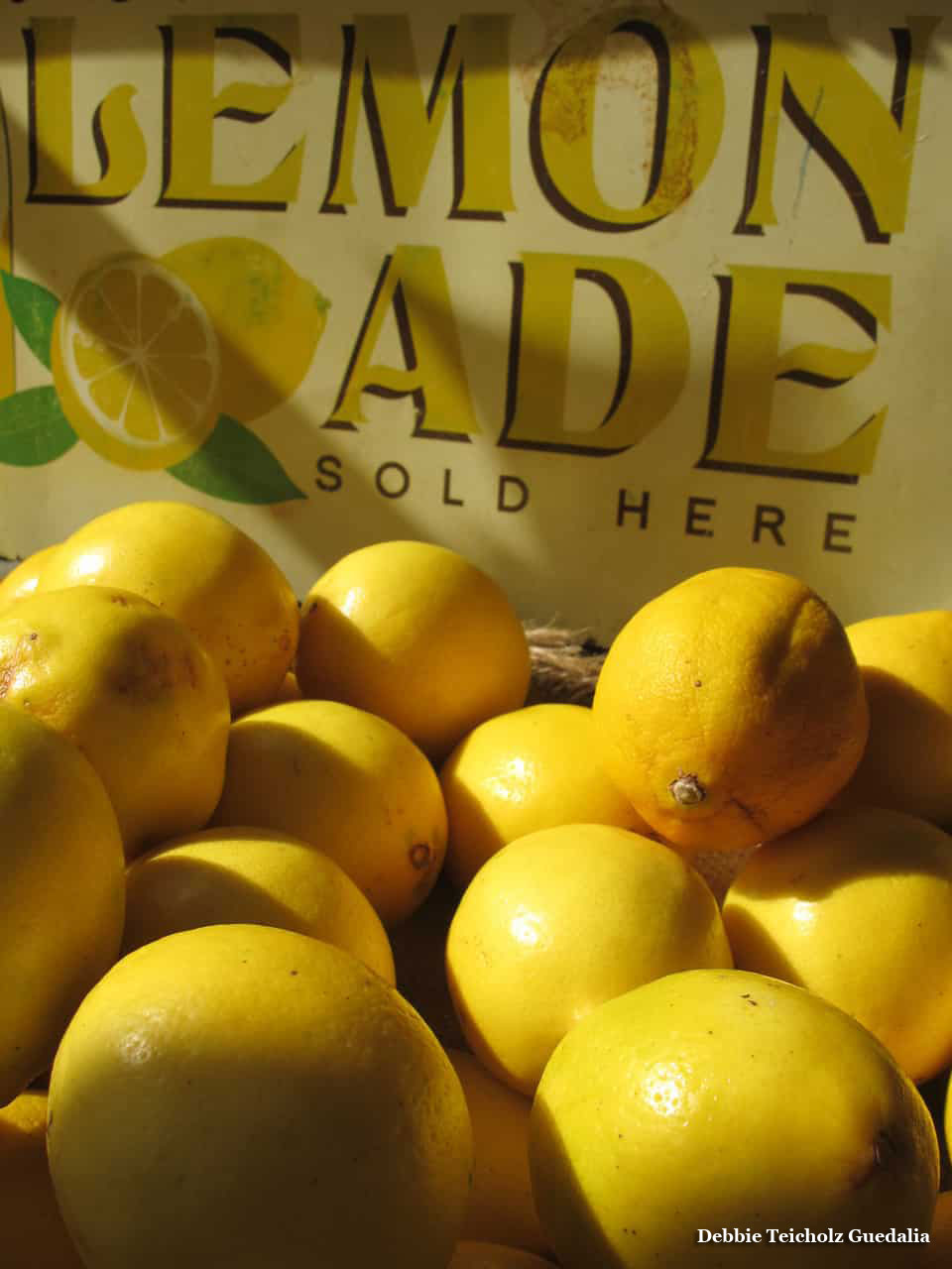 Yellow lemons in a pile in front of a hand painted Lemonade sign
